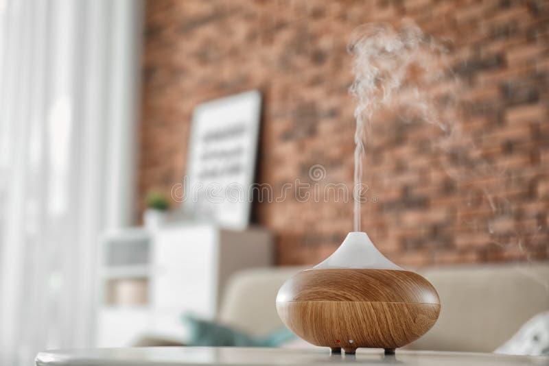 Diffusore dell'olio dell'aroma sulla tavola a casa immagini stock libere da diritti