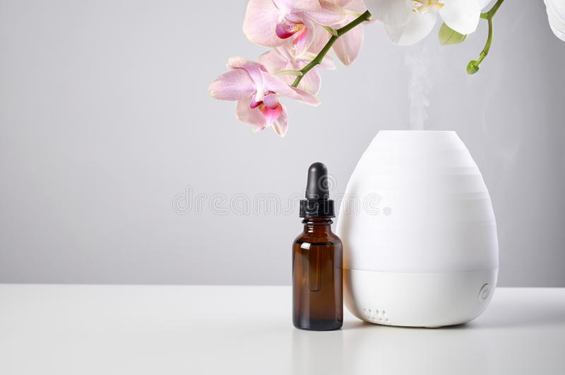 Diffusore dell'olio con i fiori ambrati di vetro dell'orchidea e della bottiglia sulla tavola bianca fotografie stock libere da diritti