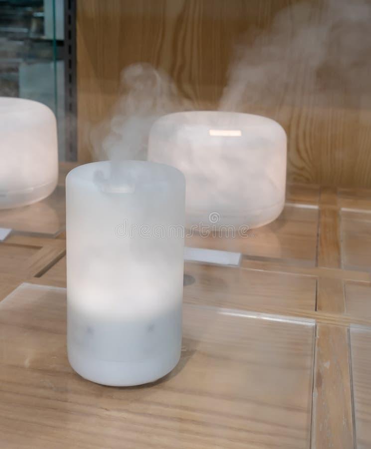 Diffusore elettrico dell'olio dell'aroma sul pavimento di legno fotografie stock