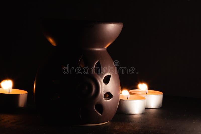 Diffusore tradizionale dell'aroma con le candele nella parte posteriore, immagine scura con alto contrasto fotografie stock