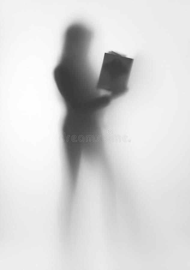 Diffuus de vormsilhouet van het vrouwenlichaam, met boek in handen stock foto's