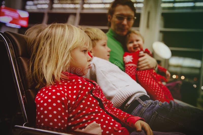 Dificultades en viaje con espera infeliz niño-enojada de la niña en aeropuerto con la familia fotos de archivo libres de regalías