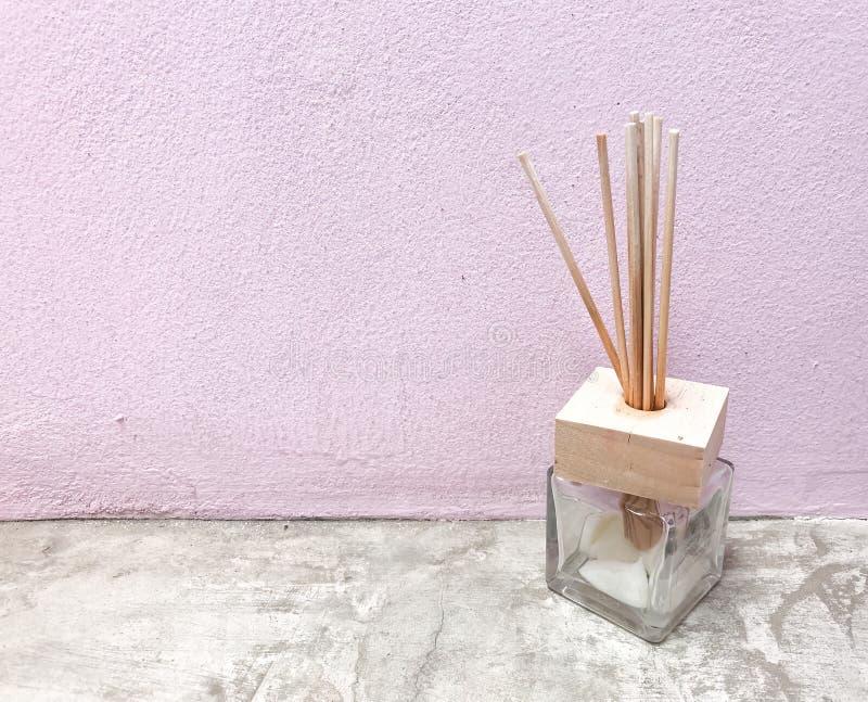 Difusor do junco do aroma contra a parede cor-de-rosa no assoalho cinzento do cimento imagem de stock
