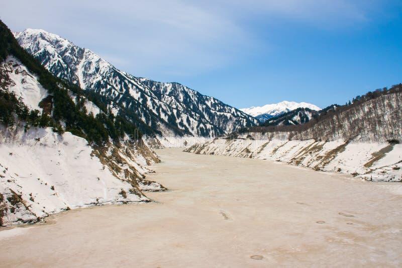 Diga di Kurobe sul fiume di Kurobe e sul bello itinerario alpino di Tateyama Kurobe del paesaggio le montagne della neve con il f fotografie stock libere da diritti