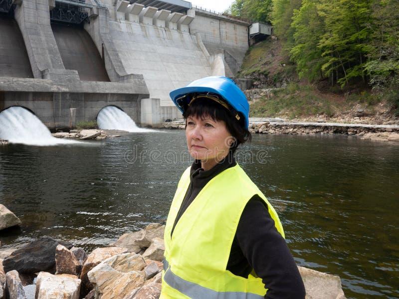 Diga e turbine di una centrale idroelettrica con gli scorrimenti dell'acqua di caduta e della donna in casco fotografia stock libera da diritti