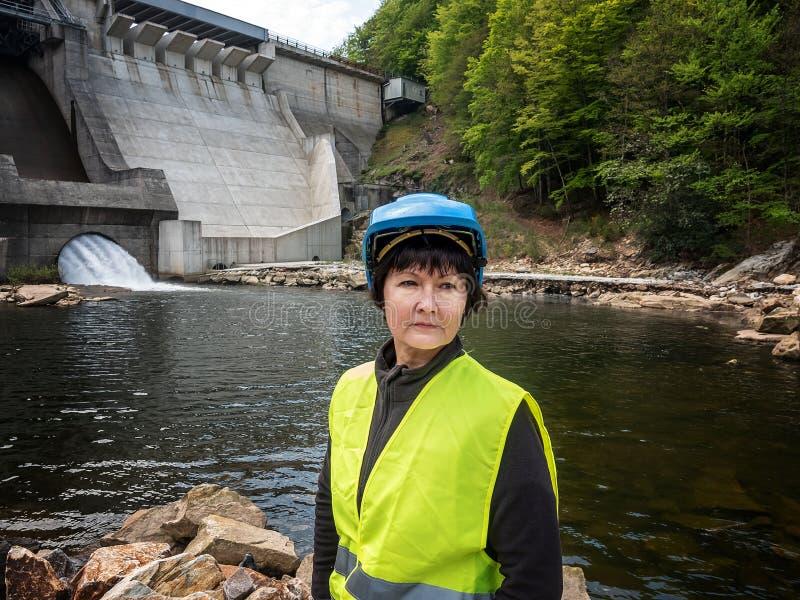 Diga e turbine di una centrale idroelettrica con gli scorrimenti dell'acqua di caduta e della donna in casco immagine stock