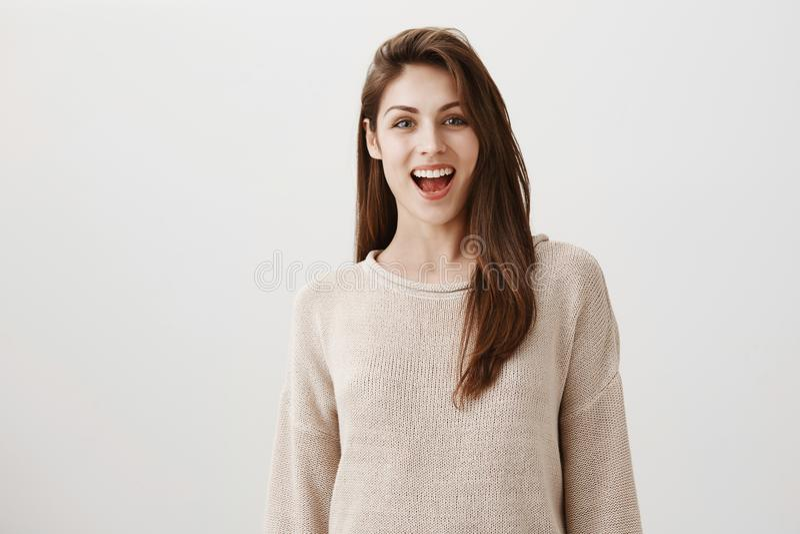 Diga el queso y la sonrisa extensamente a la cámara Retrato de la hembra europea morena bonita en suéter casual, sonriendo amplia imágenes de archivo libres de regalías
