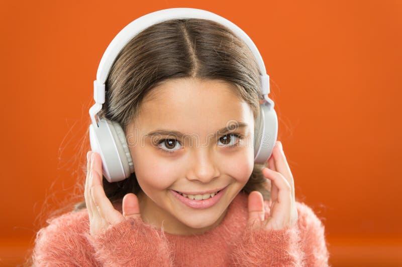 Diga-me o que você escuta, e eu di-lo-ei que você é A crian?a pequena bonito da menina veste fones de ouvido para escutar m?sica  imagem de stock royalty free