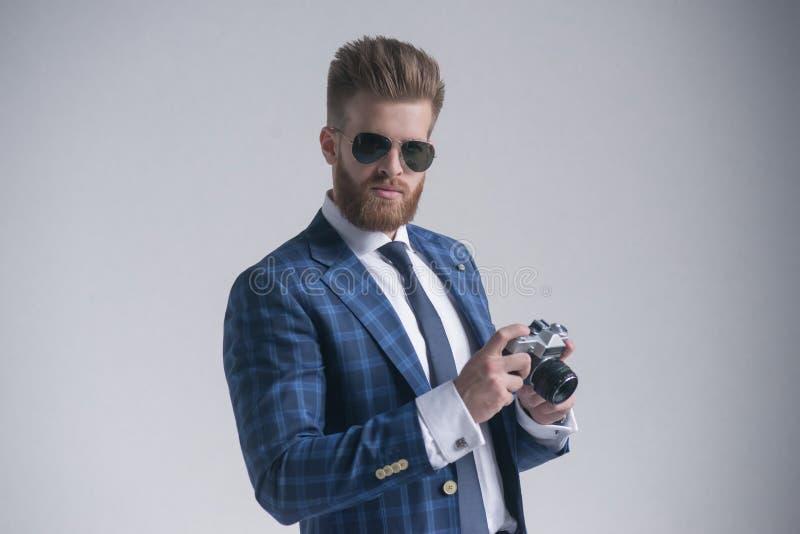Diga o homem novo considerável do queijo no terno completo e os óculos de sol que guardam a câmera velha ao estar contra o fundo  foto de stock royalty free