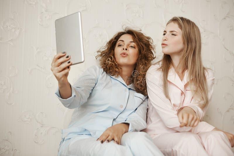 Diga o mwah à câmera Amiga dois bonita que senta-se em casa no nightwear que tem o divertimento ao tomar o selfie com digital fotografia de stock