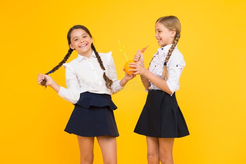 Diga sim à saúde Alunos pequenos que bebem o suco dos frutos alaranjados para sua saúde no fundo amarelo foto de stock