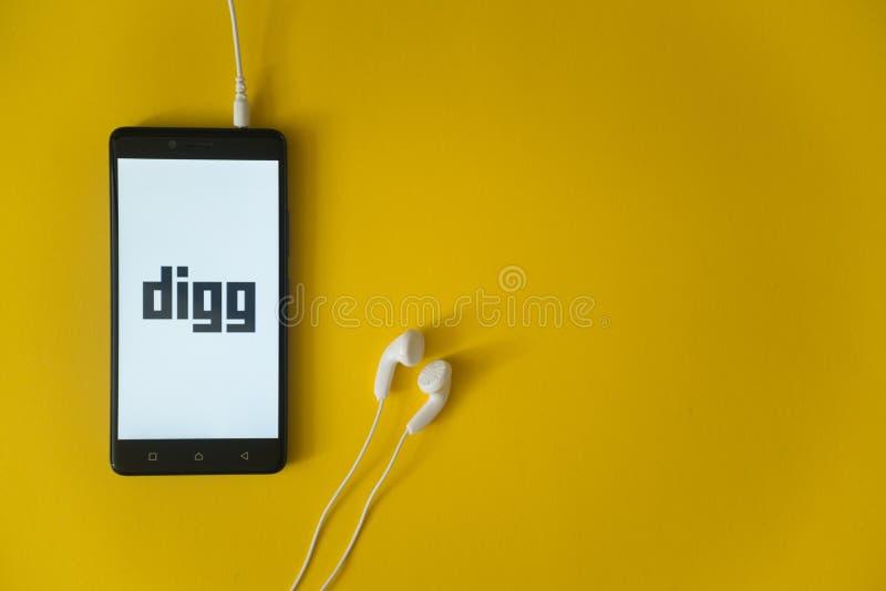Diggembleem op het smartphonescherm op gele achtergrond stock fotografie