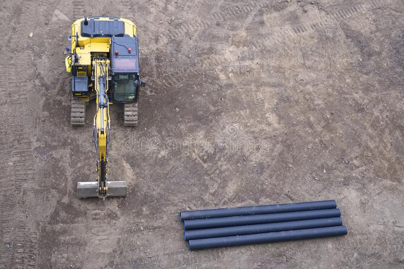 Digger excavator construction building site banner view from above miniature rubber tracks yellow vehicle in operation excavating royalty free stock images
