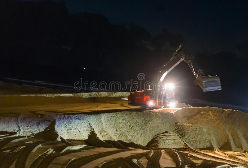 Digger excavator working at night time moving the ground at the beach for maintenance royalty free stock photo