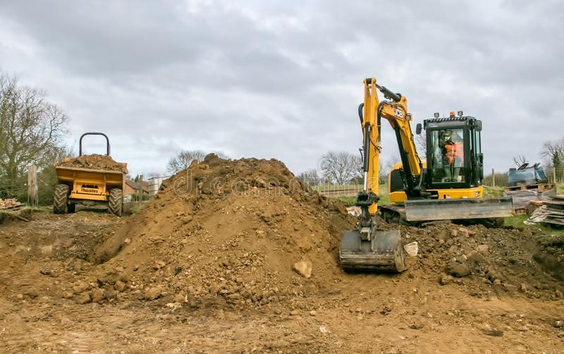 A digger moving soil. A digger excavator dumping soil while laying footings with dumper truck stock photos