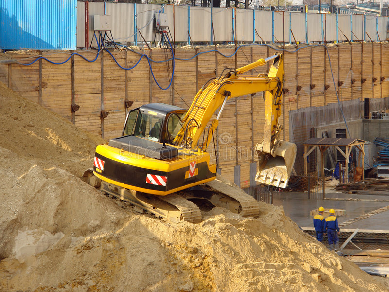 Digger on sand heap stock photography