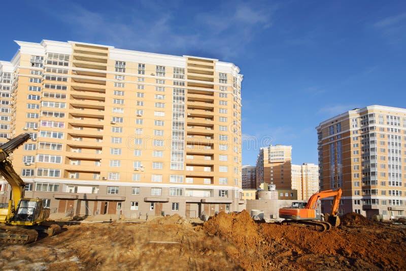 Diggers dig ground near high multi-storey building stock photos