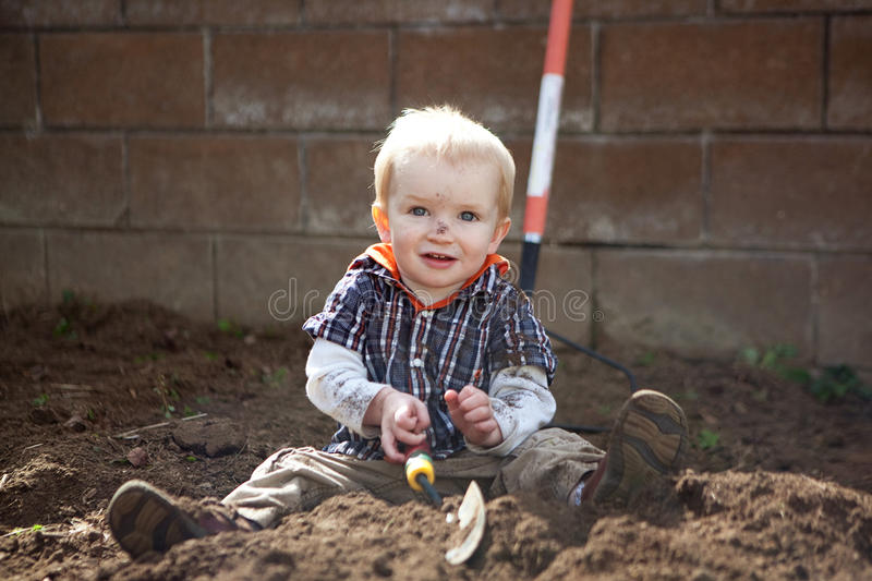 Digging. Boy digging in a garden stock photo