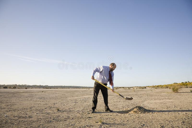 Digging a Hole Concept. A businessman digging a hole, various business concepts royalty free stock photo