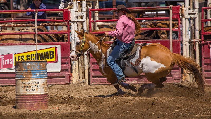 Digging in and Moving Fast. A cowgirl clears a barrel during a barrel racing event. The rodeo in Cottonwood, California is a popular event on Mother's Day royalty free stock image