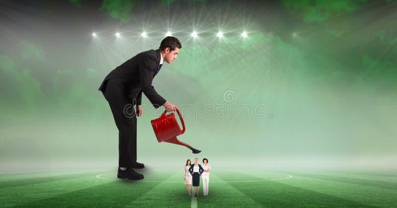 Digitaal samengesteld beeld van zakenman die vrouwelijke werknemers water geven bij stadion stock foto