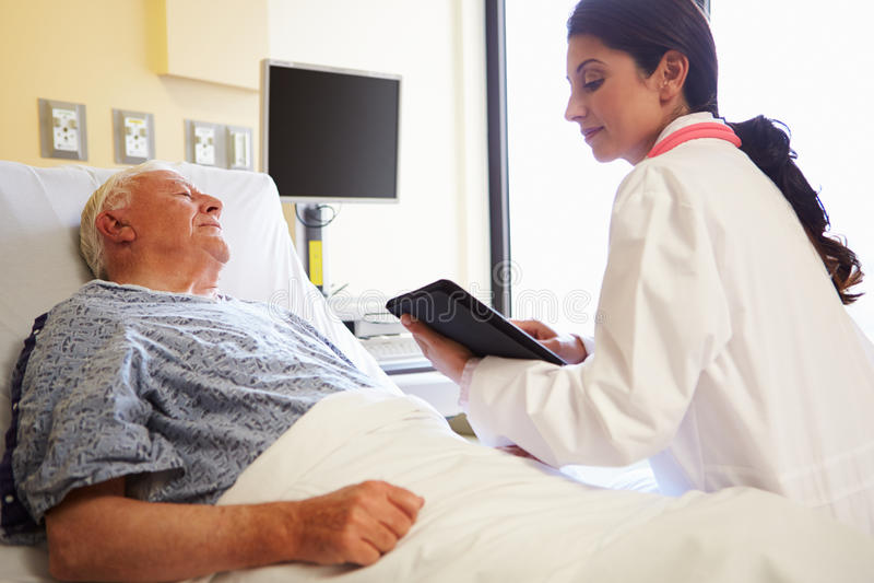 With Digital对患者的Tablet Talking医生在医院 免版税库存照片