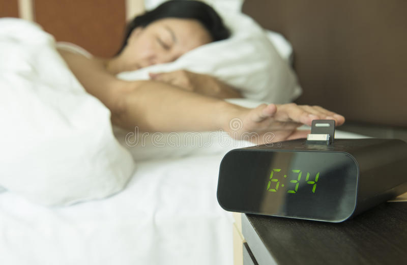 Digital alarm clock. Young woman reach out one`s hand Press the button to turn off the digital alarm clock in morning royalty free stock image