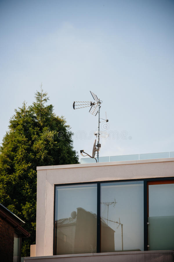 Digital and analog antenna next to satellite dish on the same ma. St on the rooftoop of a modern building stock photos