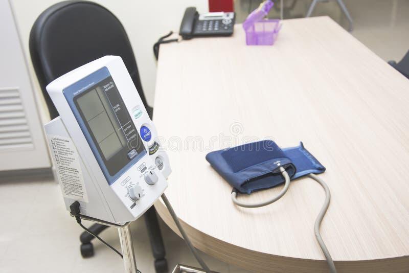 Digital-Blutdruck-Monitorkubikfüße auf dem Schreibtisch stockbilder