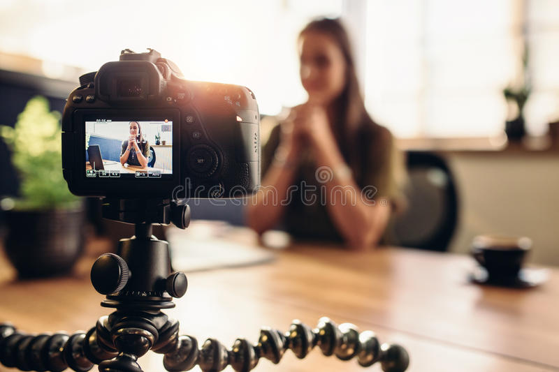 Digital camera on flexible tripod recording a video of woman at. Female vlogger recording content for her video blog. Young woman in focus on digital camera royalty free stock photography