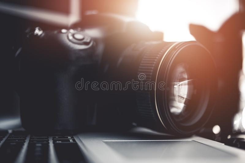 Digital Camera on the Laptop. Computer Closeup Photo. Photographers Desk royalty free stock images