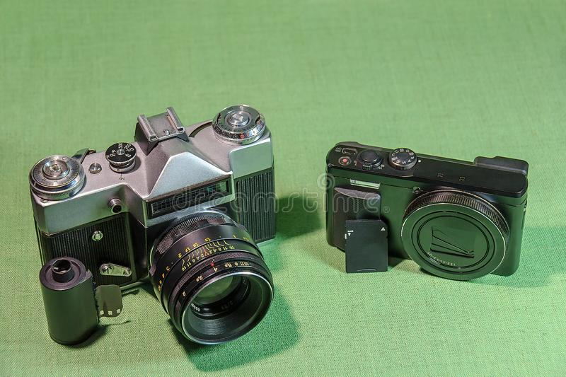 Digital camera versus film camera. Two cameras - retro and modern with data carriers on a green background stock photography