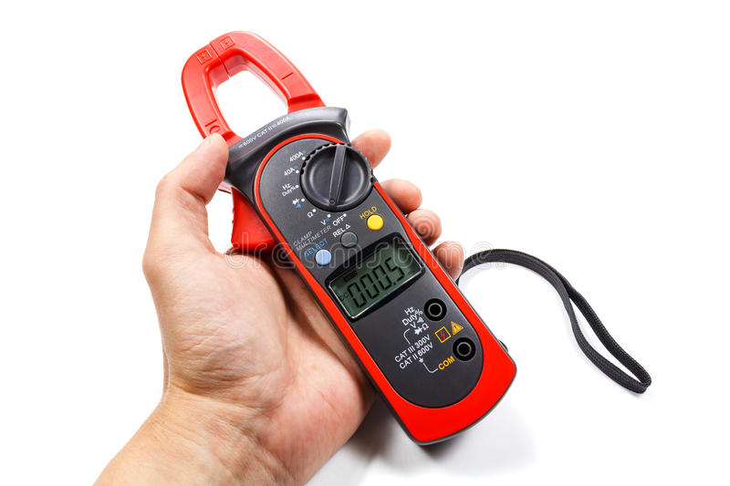 Digital clamp multimeter in man`s hand on a white background stock image