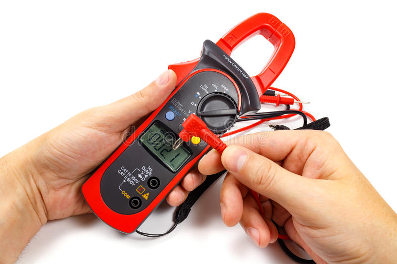 Digital clamp multimeter with probes in man`s hand on a white background royalty free stock photos