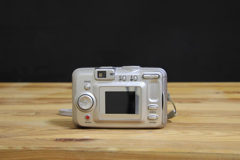 Digital compact camera on wooden board with black background and hand strap on white wooden board.  stock images