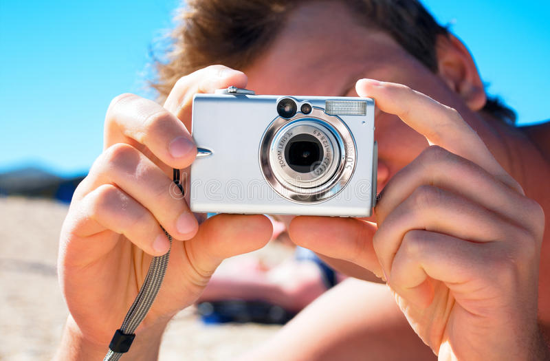 Digital compact photo camera in hands. On the beach royalty free stock images