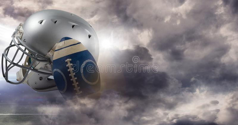 American football and helmet with sky transition. Digital composite of American football and helmet with sky transition stock photo