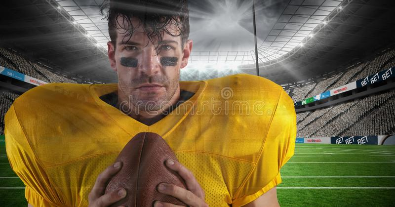 american football player standing in stadium holding the ball royalty free stock image