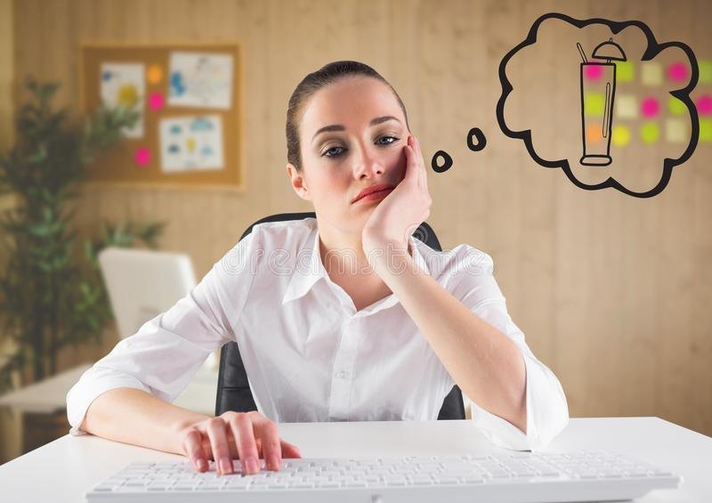 Bored business woman at desk dreaming of cocktail against blurry office stock photo