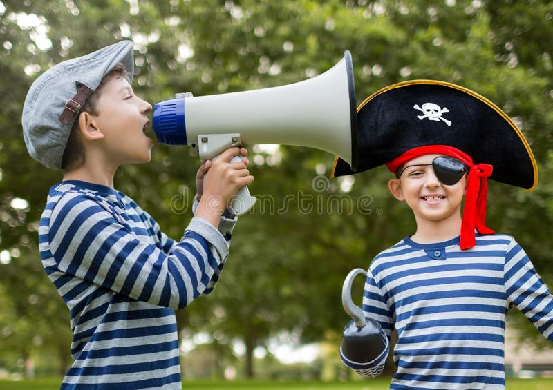 Boy holding megaphone and pirate in front of trees royalty free stock photo