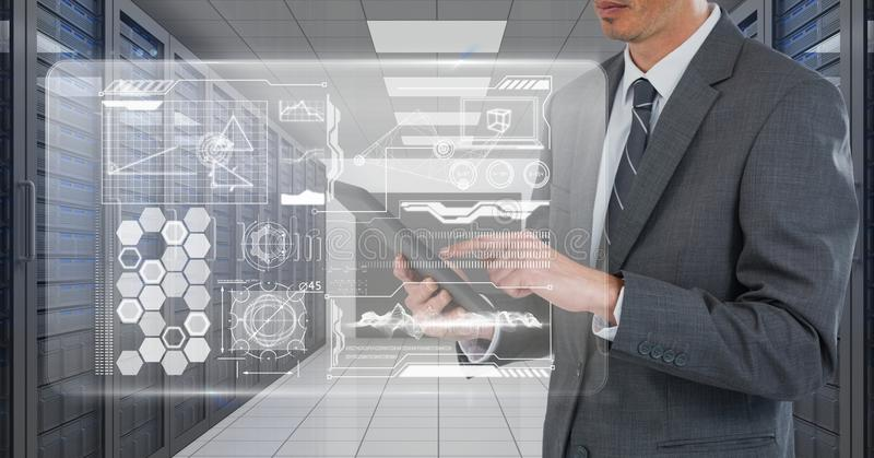 Business man holding a tablet and graphics in server room. Digital composite of Business man holding a tablet and graphics in server room royalty free stock image