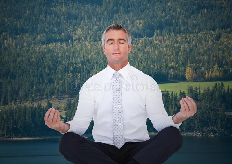 Business man meditating against trees and river. Digital composite of Business man meditating against trees and river stock photo