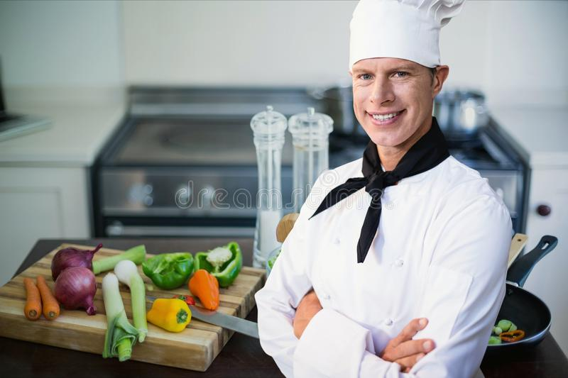Chef standing in kitchen. Digital composite of chef standing in kitchen stock image