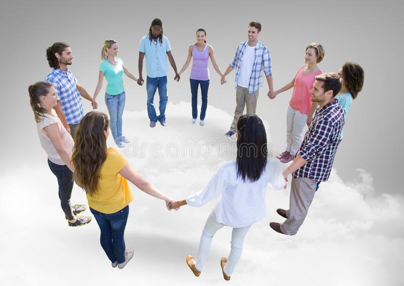 Circle of people holding hands together on clouds stock photography