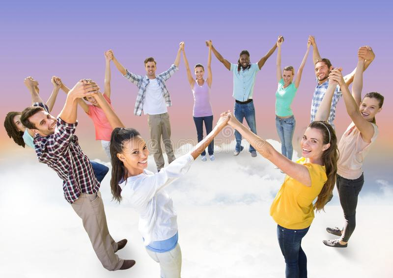 Circle of people holding hands together in clouds royalty free stock images