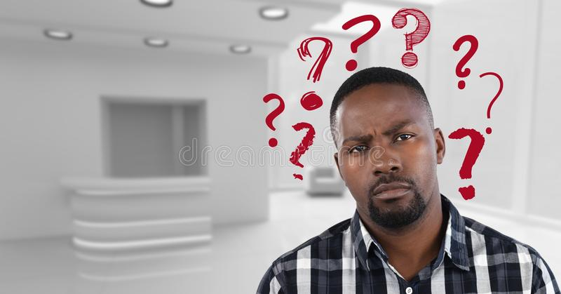 Confused man in a white office with red question marks stock photography