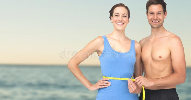 Couple measuring weight with measuring tape on waist on Summer beach royalty free stock images