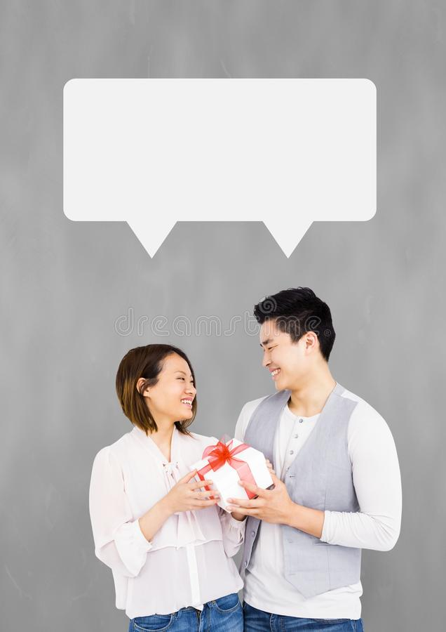 Couple with speech bubble smiling against grey background royalty free stock images