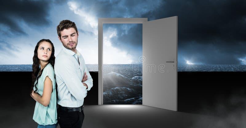 Couple standing by open door with surreal dark sea glow and sky stock photos