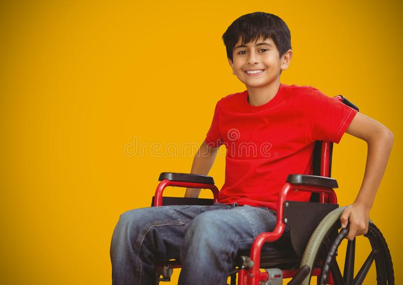 Disabled boy in wheelchair with bright yellow background royalty free stock photography